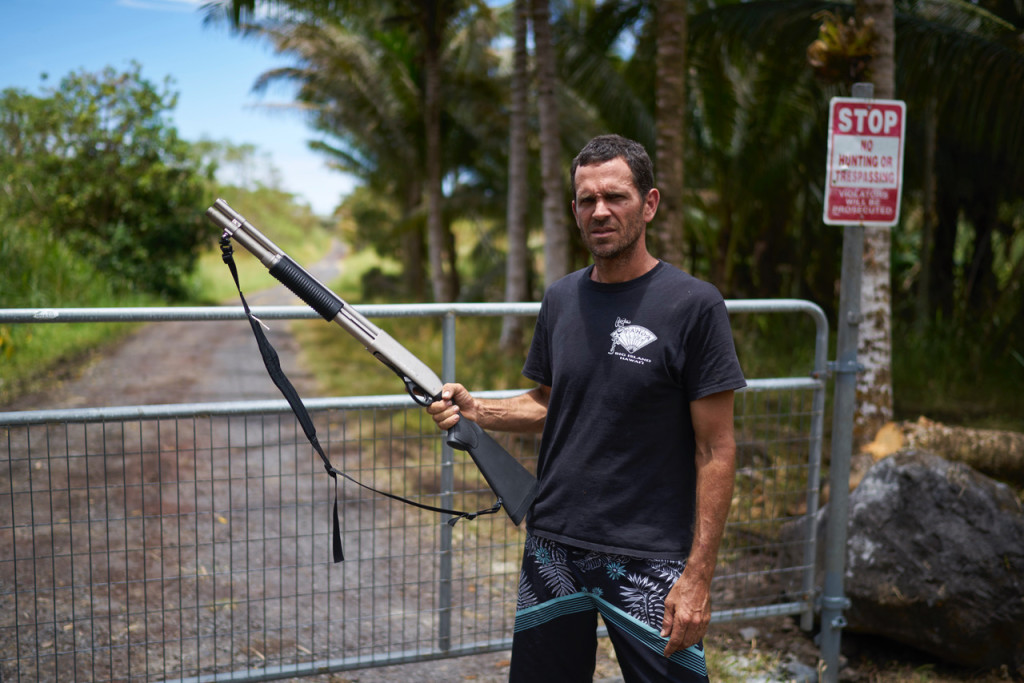 May 15, 2018. Kilauea Volcano, Hawaii. Organic produce at the 20 acre Johnson Family Farm has been destroyed due to the toxic air quality near the Kilauea Volcano. Pictured is Braha Johnson looking out for looters at the farm entrance, armed with a shotgun. Photo copyright John Chapple / www.JohnChapple.com
